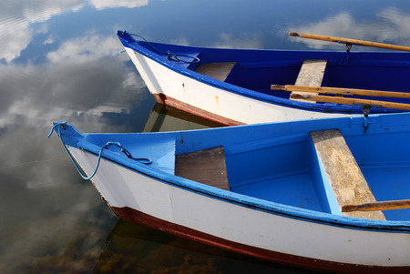 Sky reflection and wooden blue boats awaiting tourists at the jetty Stock Photo