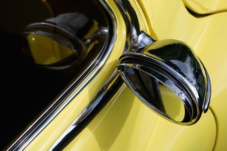 retrovisor: Antiguo espejo retrovisor en la parte de un vintage de color amarillo auto.