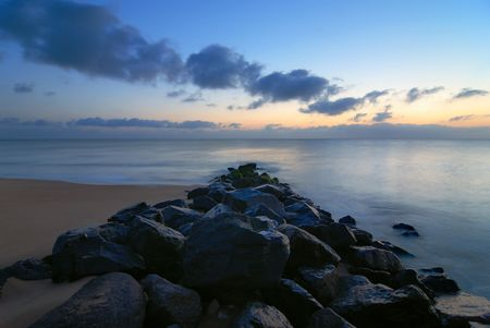 Morning long exposure on the beach on a  seawall. Stock Photo