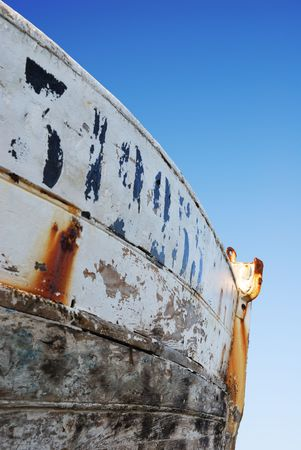 Side view a rusty prow against a deep blue sky photo