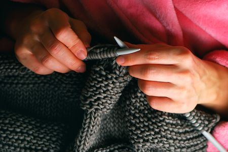 Young woman hands knitting a grey pullover