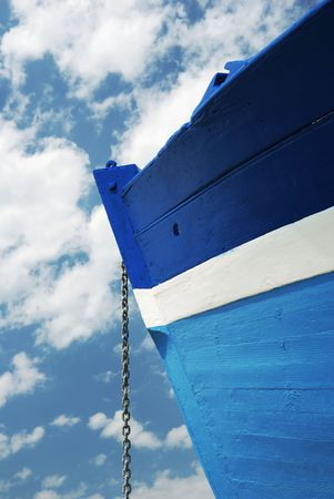 Side view of a wooden white and blue fisherman boat with its chain anchor under a cloudy sky