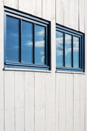fanlight: White facade and Sky Reflexion through blue windows Stock Photo