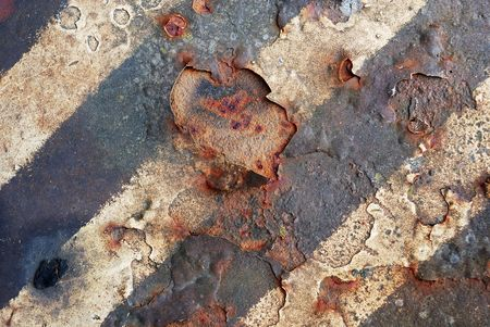 Growing rust under grey and yellow painted lines. Stock Photo