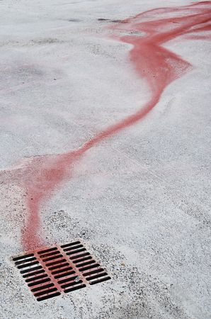 Red ink flow running down to a manhole cover