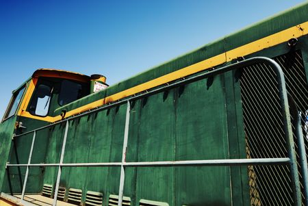 Side view of an old green diesel locomotive under blue sky photo