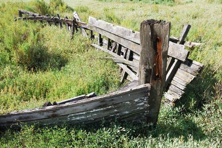 Side view of a very old boat aground in the green land. Stock Photo