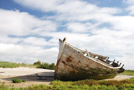 old boat: White boat wreck lying on the sand.
