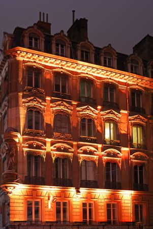Orange illuminated night facade in old center city.  Stock Photo