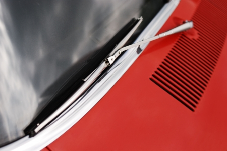 Windscreen wiper and sky reflection on a red car. Stock Photo