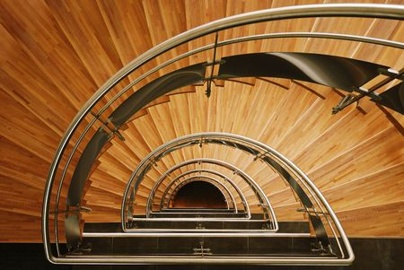 Down view of a semi elliptical interior wooden staircase