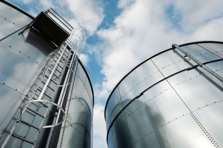 Low-angle shot of ladder and tanks refinery. Stock Photo