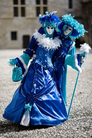 Couple with carnival costumes and masks in a castle court (AnnecyFrance) Stock Photo