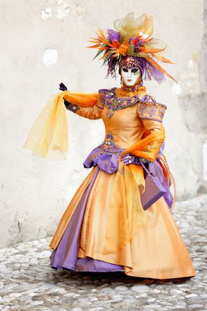 period costume: Orange dress costume and masks walking in the street (AnnecyFrance) Stock Photo
