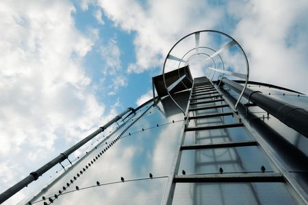 Low-angle shot of ladder on tank refinery.