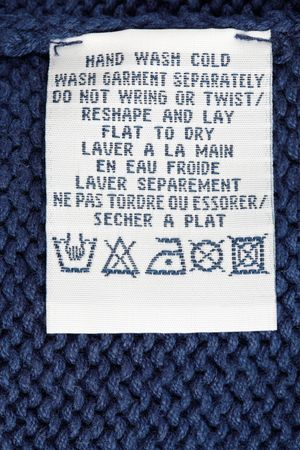 Close up view of a laundry advice clothing tag isolated on a blue pullover