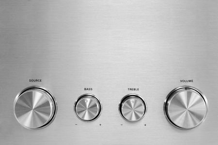 Four isolated gray hifi knobs from a stereo amplifier Stock Photo