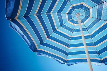 Blue striped parasol under polarized hot blue sky Stock Photo