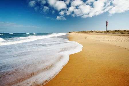 Wide angle and polarized view of a beach and Coubres lighthouse in the background. photo