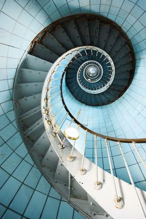 A spiral staircase going up with blue tiled wall (Charente Maritime  France) Stock Photo