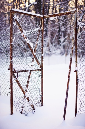 Broken fence under snow - Open wire gate with broken fence under snow morning conditions photo