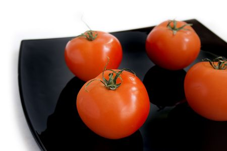 Red tomatoes on the black plate isolated on white Фото со стока