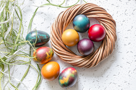 contrast floral: Colorful Easter eggs on white background and raffia