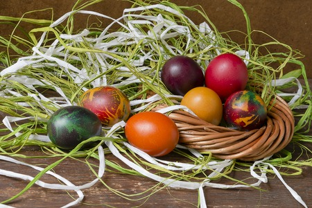 contrast floral: Colorful Easter eggs and raffia on wooden table