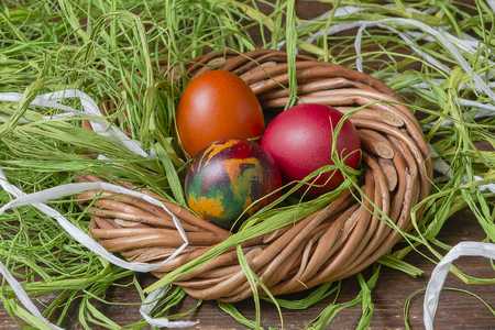 Colorful Easter eggs and raffia on wooden table