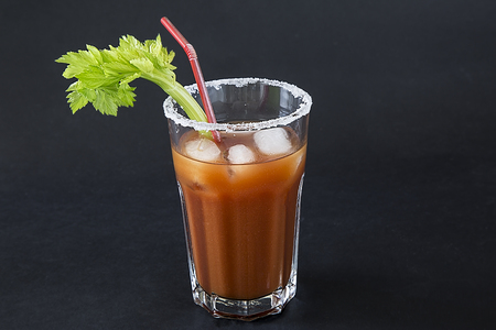 a glass with a cocktail Bloody Merry with ice and a sprig of celery on a black background, the top of the glass is decorated with salt Stock Photo
