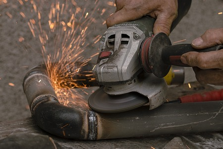 worker cuts a metal pipe by means of the abrasive tool with sparks