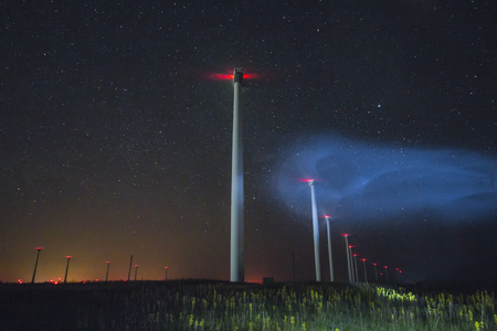 beautiful night photo of wind generators and stars with abstract lighting Stock Photo