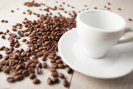 empty coffee cup with scattered coffee beans photo