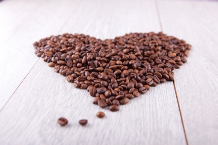 Heart of coffee beans on a wooden background photo