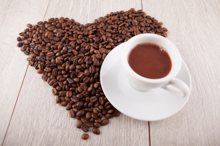 Heart of coffee beans with a cup filled with coffee photo