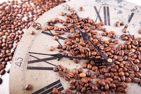 picture of coffee beans scattered on a vintage clock photo