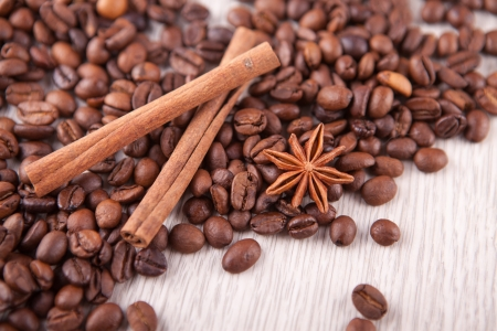 two cinnamon sticks and scattered coffee beans photo