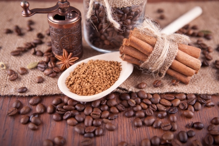 coffee beans, cinnamon sticks and ground coffee on a wooden board