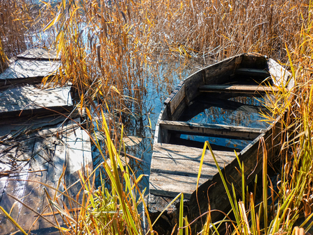 Forgotten flooded boat on the autumn lake