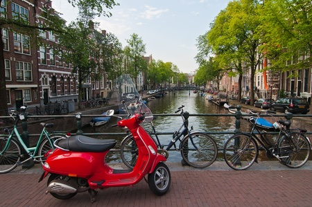 bicycles and  red moped  on the bridge photo