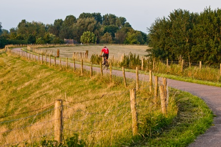cyclist rides along a winding path in the early morning photo