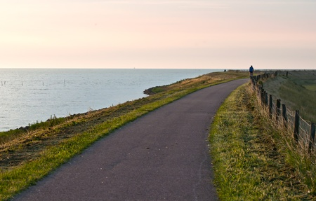 A lone cyclist rides along the path early in the morning photo
