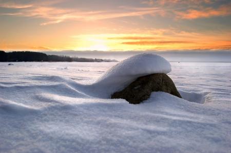 stone under snow at background sundown Stock Photo