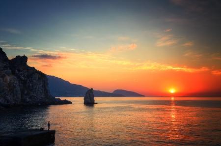 the morning sun rises over the warm sea, warms fisherman Stock Photo
