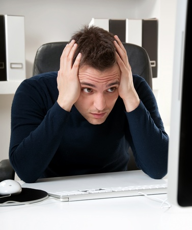 Young man thinking in front of his computer in the office ambient Stock Photo - 9119255