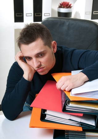 catalogues: A young businessman tired on his top of catalogues