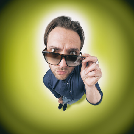 discoteque: Funny man looking through his sunglasses with opened eyeys