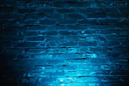 Empty brick wall with blue neon light background Foto de archivo