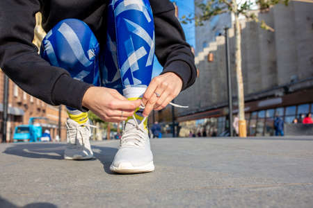 Female fitness runner tying sportshoe laces. Close-up hands and legs.