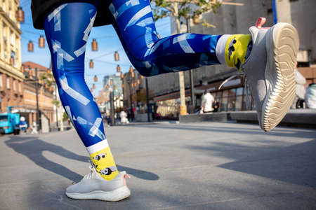 Close-up female legs in bright blue leggins and yellow socks running outdoors. Stock fotó